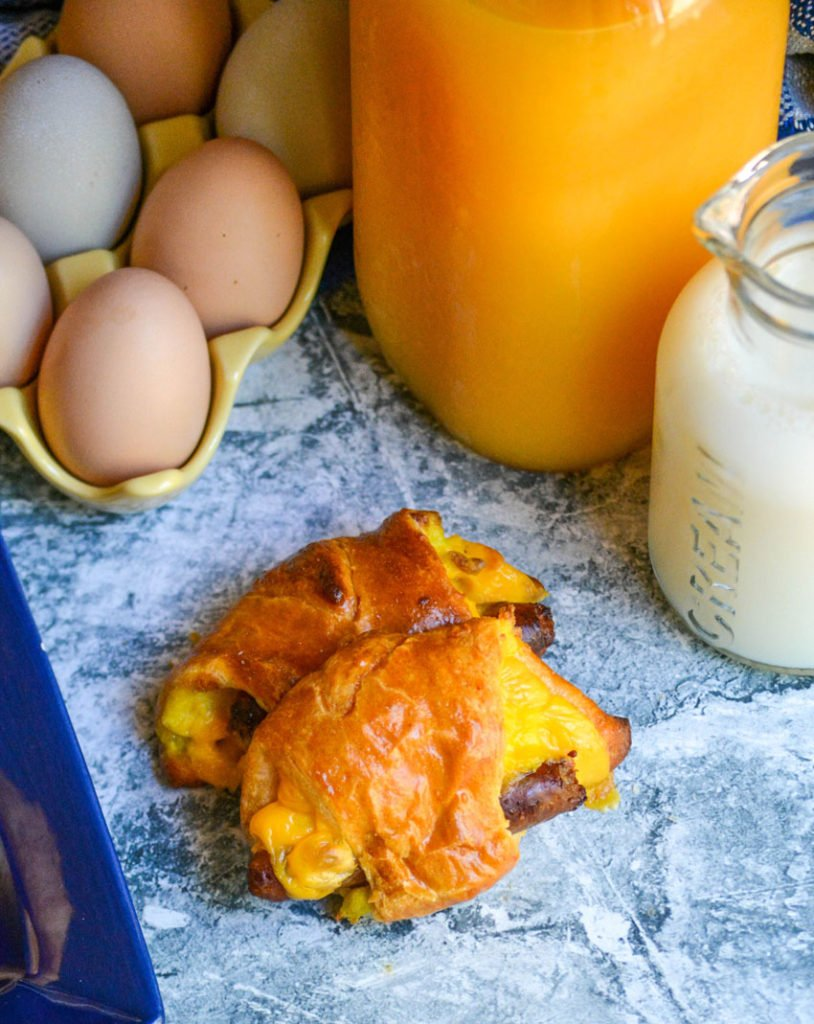 sausage egg and cheese breakfast rolls shown on a blue background