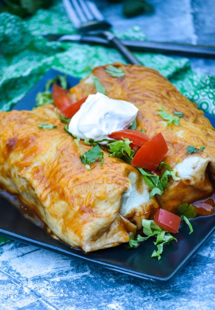 two wet burritos shown on a black square plate topped with cilantro leaves, chopped tomatoes, and sour cream