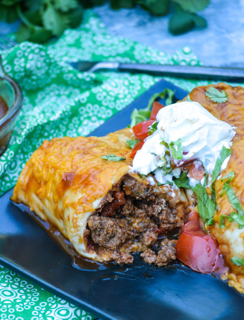 a wet burrito on a square black plate shown cut in half to reveal the ground beef filling inside