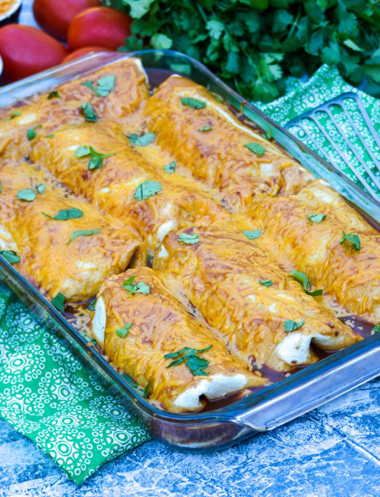 wet burritos smothered with sauce and cheese shown in a glass baking dish