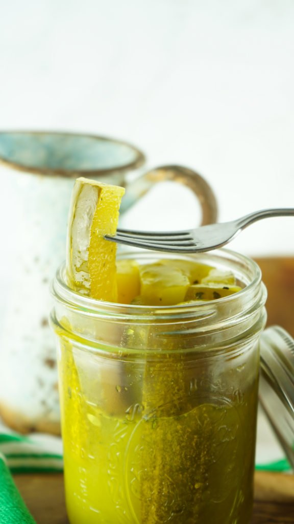a fork lifting a seasoned ranch pickle out of a glass mason jar