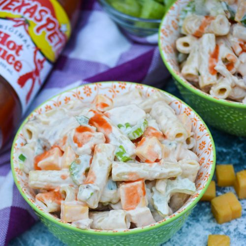 buffalo chicken pasta salad shown served in small green bowls with a drizzle of hot sauce