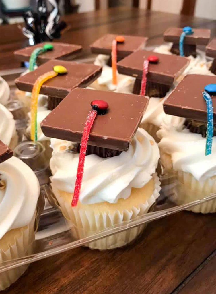 graduation cap cupcakes sitting in a clear plastic cupcake container