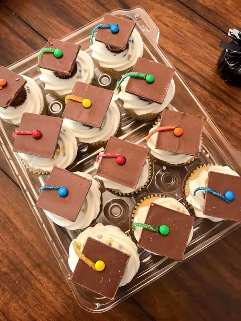 an overhead shot showing graduation cap cupcakes in a clear plastic cupcake holder on a wooden table