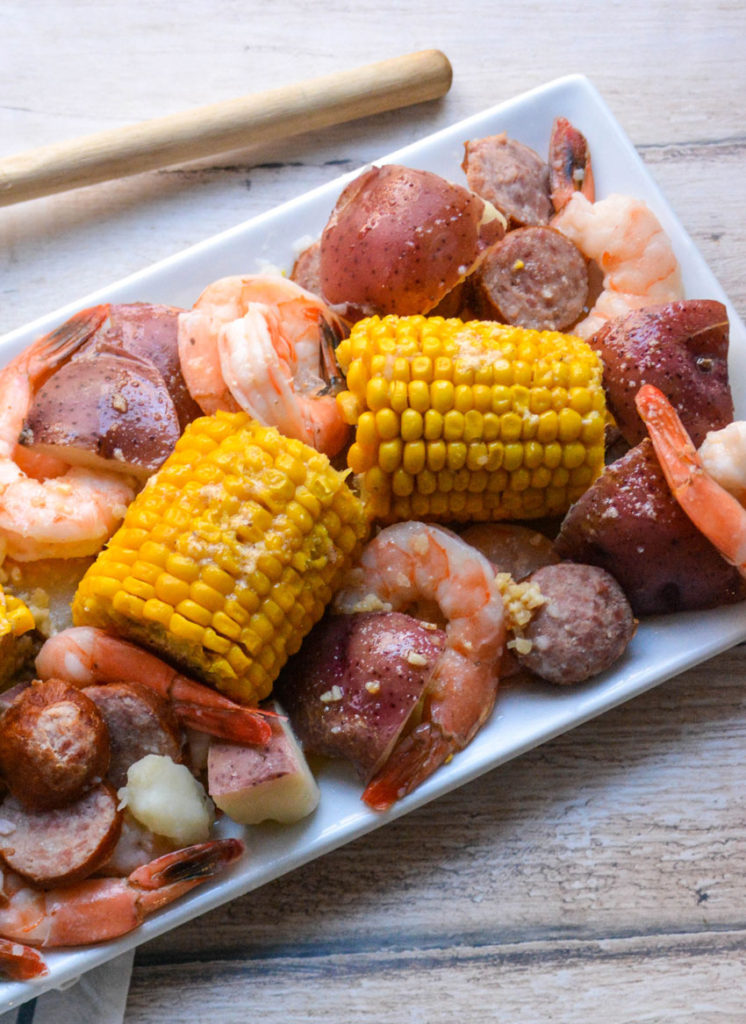 a white rectangular plate showing instant pot shrimp boil on a wooden table top