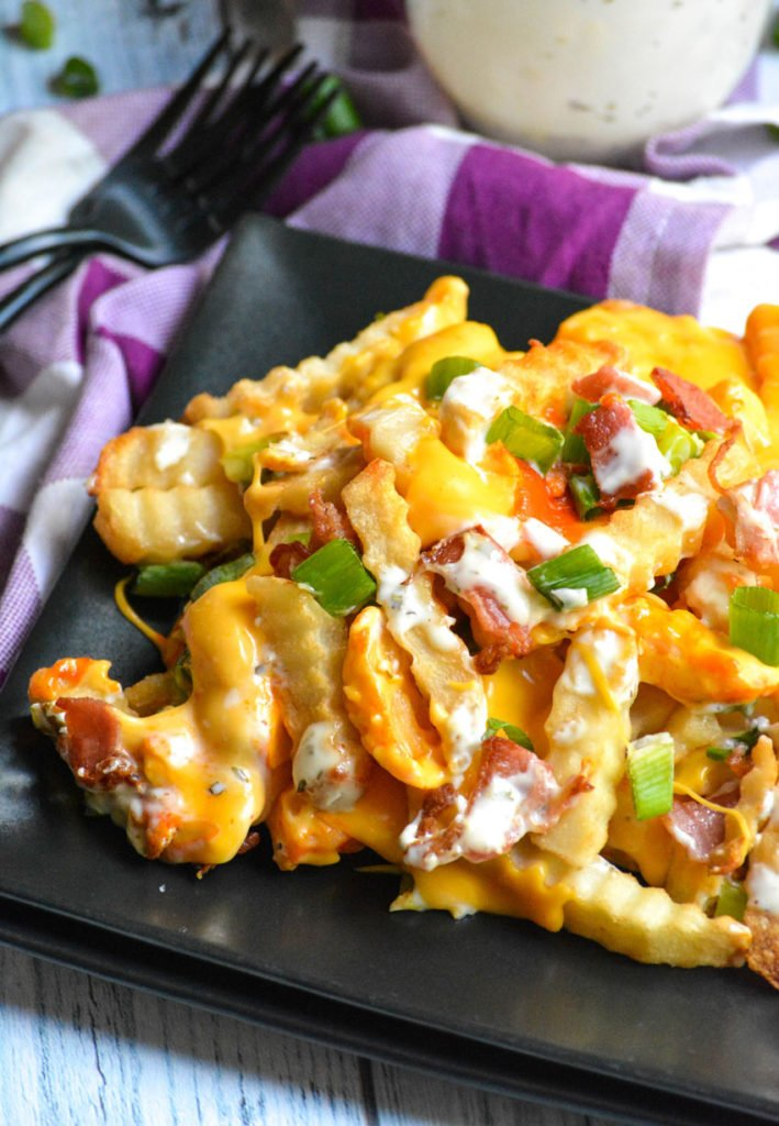 loaded buffalo cheese fries shown on a square black plate