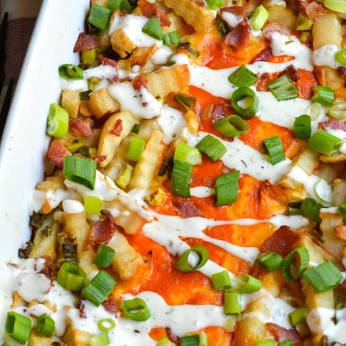 a batch of loaded buffalo cheese fries in a white casserole dish
