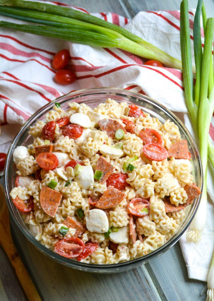 a quick and easy pasta salad with pepperoni shown in a large glass bowl with a wooden spoon on the side