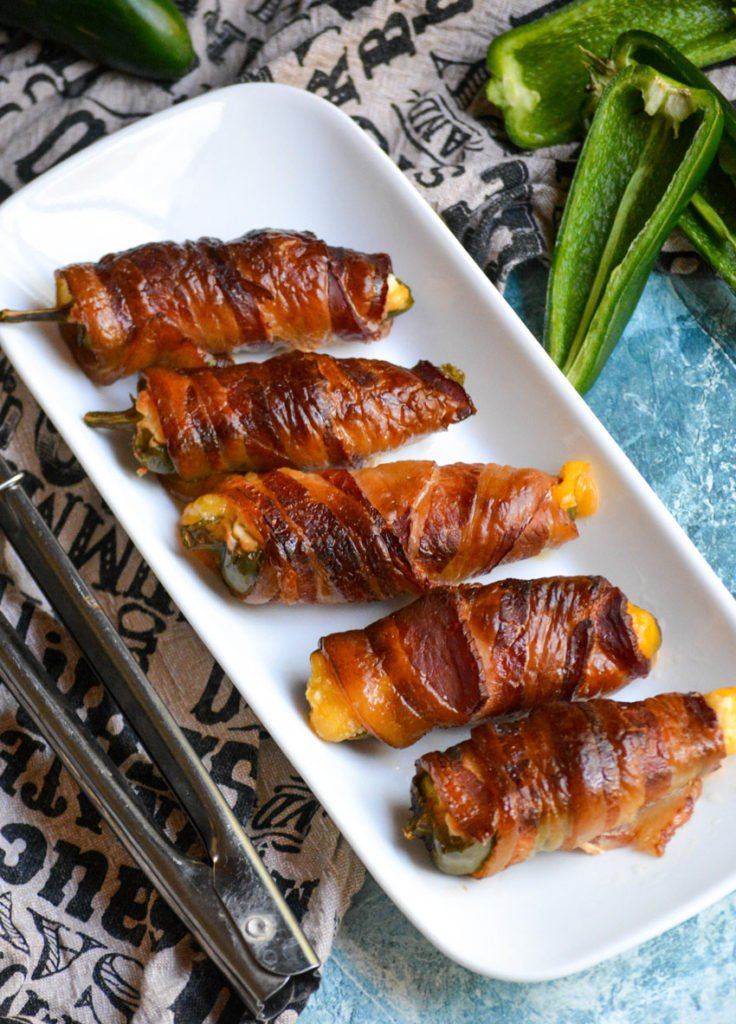 smoked jalapeno poppers lined up on a thin white platter