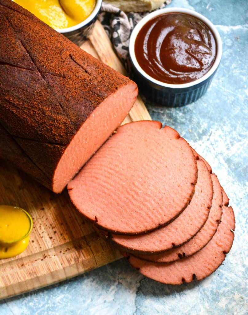 a chub of smoked bologna shown sliced on a wooden cutting board with barbecue sauce & mustard in the background