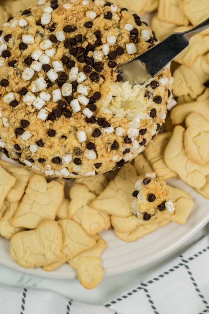 a s'mores cheese ball with a spreading knife shown stuck in the top to reveal the creamy dessert center