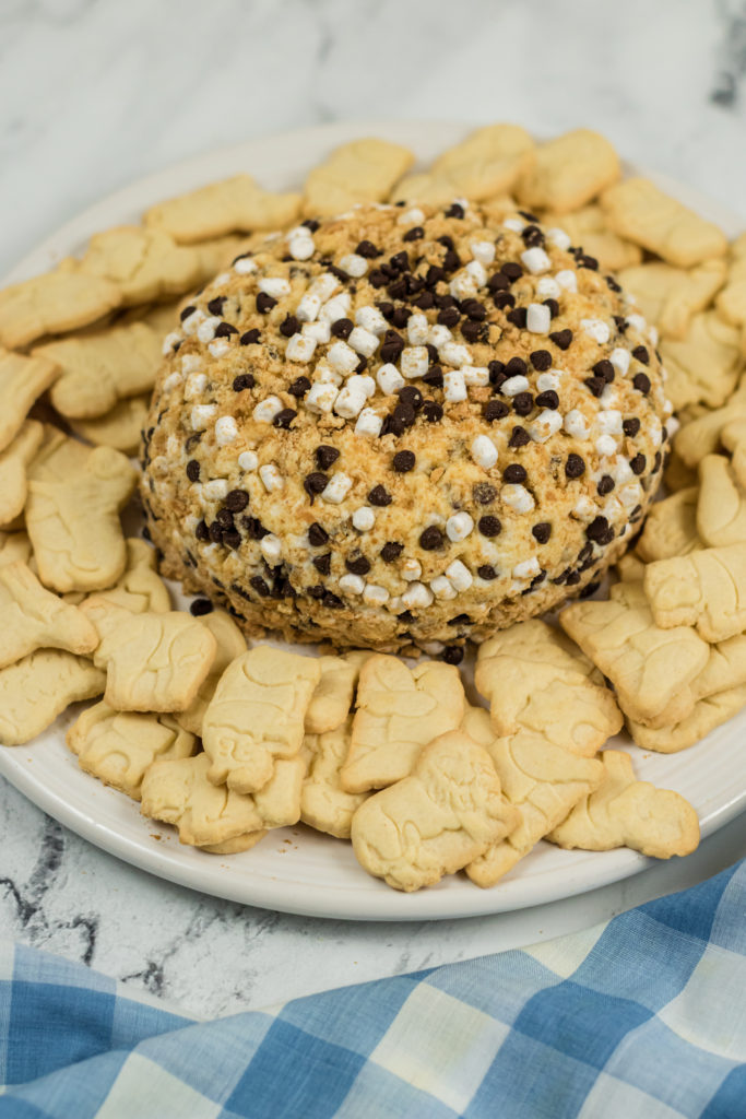 a s'mores cheese ball shown surrounded by animal crackers on a white plate