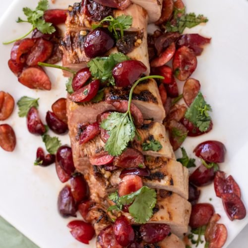 chipotle tenderloin topped with fresh cherry and cilantro salsa shown on a large white platter