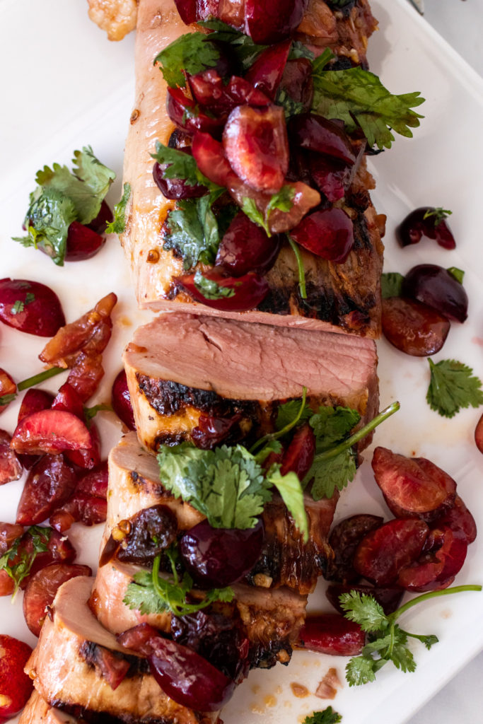 grilled chipotle pork tenderloin topped with fresh cherry and cilantro salsa & cilantro leaves shown on a large white platter