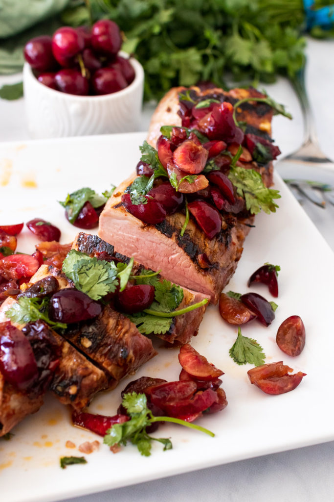 grilled chipotle pork tenderloin topped with fresh cherry and cilantro salsa shown on a large white platter