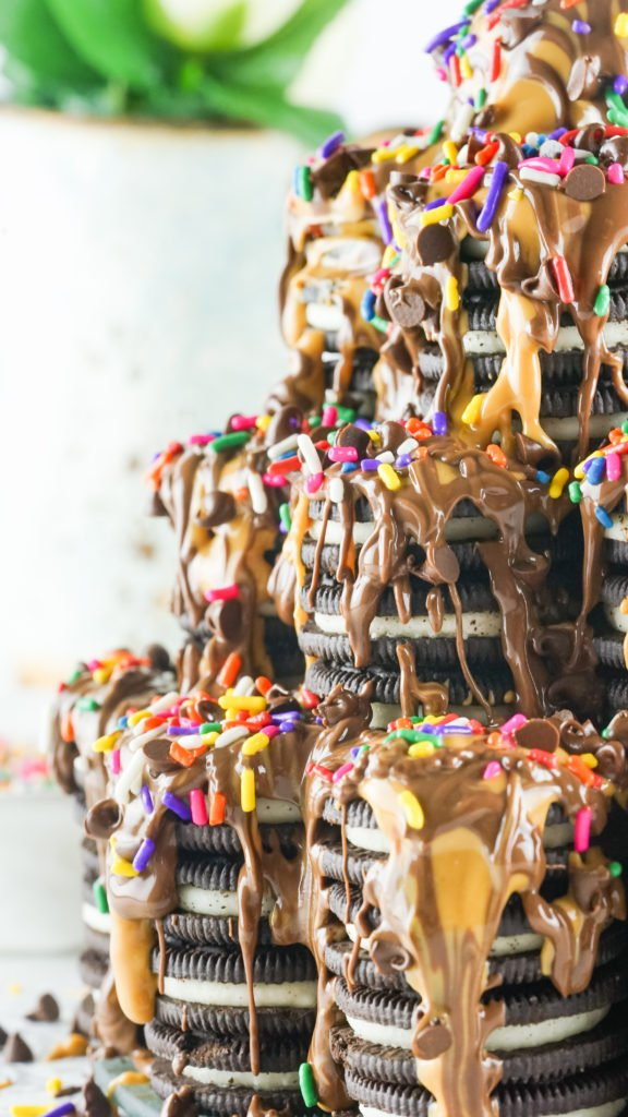 tiktok oreo tower cake covered in creamy peanut butter and rich nutella drizzles with rainbow sprinkles