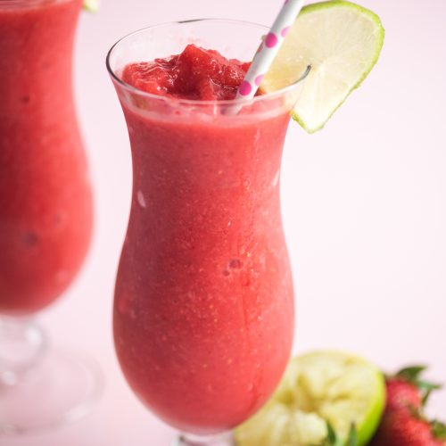 two strawberry daiquiris in glass jars garnished with lime slices and paper straws