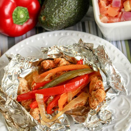 a grilled chicken fajita foil packet shown opened on a white plate