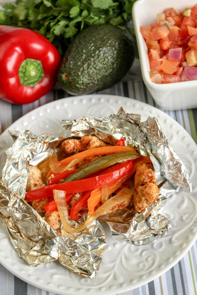 a chicken fajita foil packet shown opened on a white plate