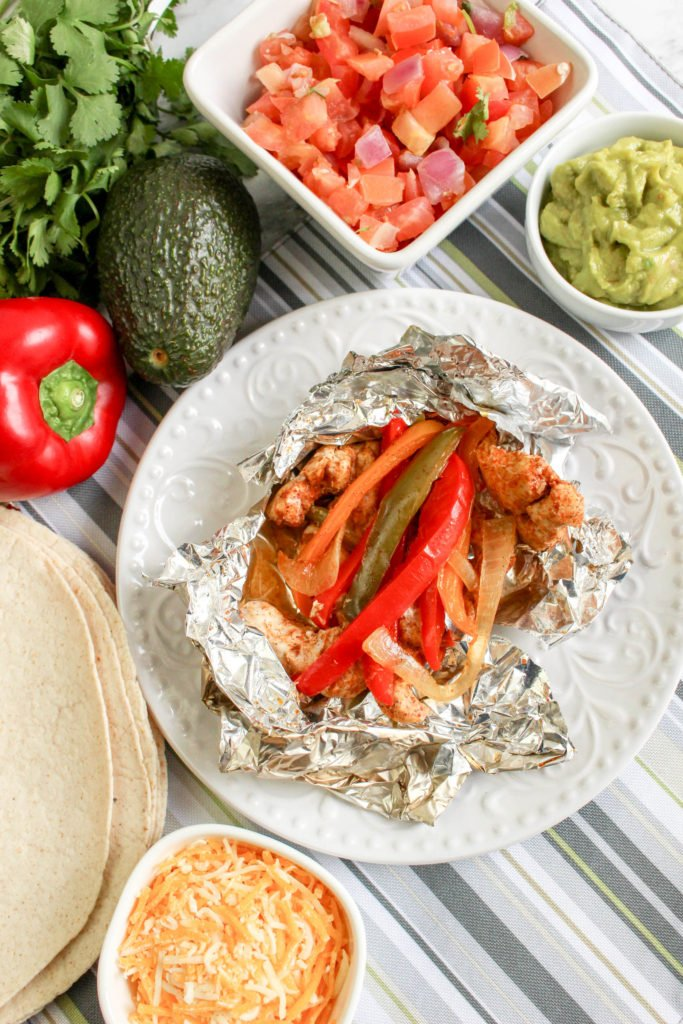 grilled chicken fajita foil packet open on a white plate surrounded by topping options