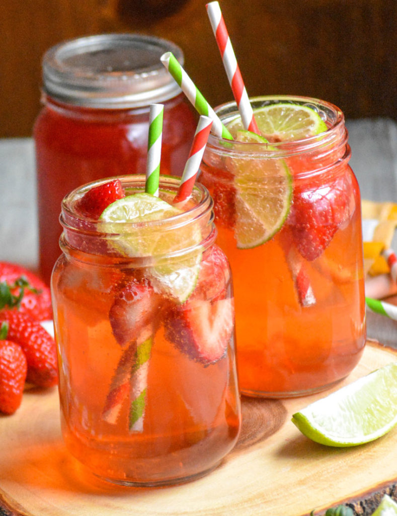 copycat sonic strawberry limeade in glass jars on a wooden cutting board