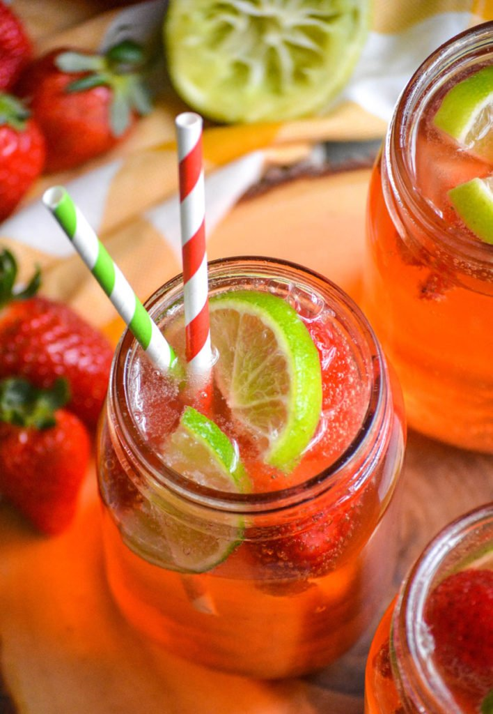a glass of strawberry limeade shown with fresh fruit garnish and striped paper straws