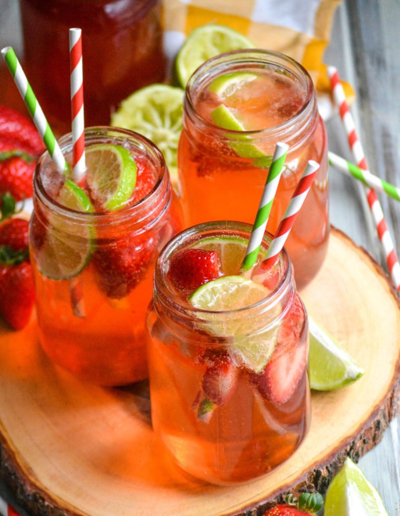 three glasses of strawberry limeade shown with fresh fruit garnish and striped paper straws