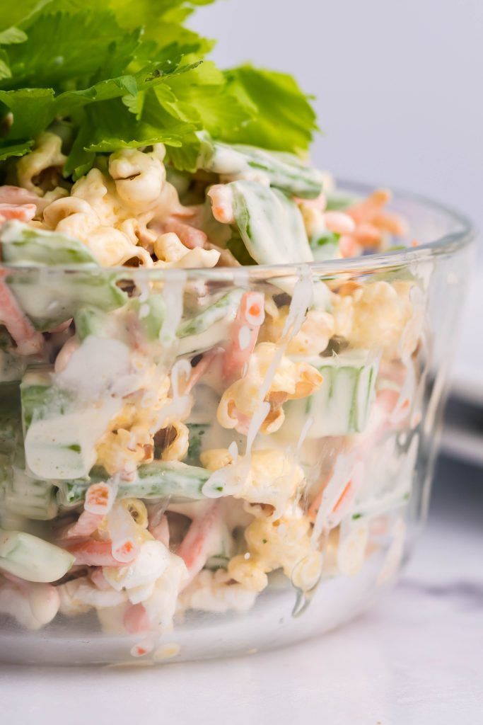 popcorn salad in a glass bowl topped with celery leaves