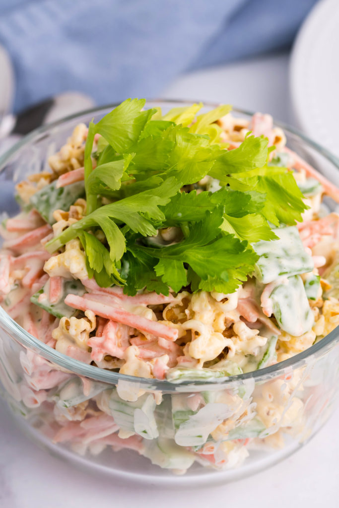popcorn salad with snap peas in a glass serving bowl & garnished with celery leaves