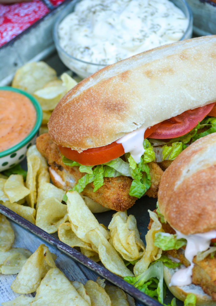 two fish stick po boy sandwiches served on a metal tray with chips and a bowl of tartar sauce