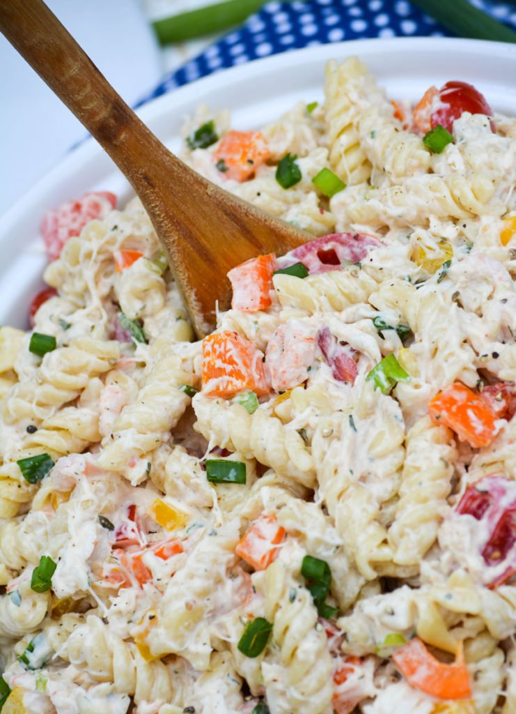 seafood pasta salad served in a white bowl with a wooden spoon stuck in the center