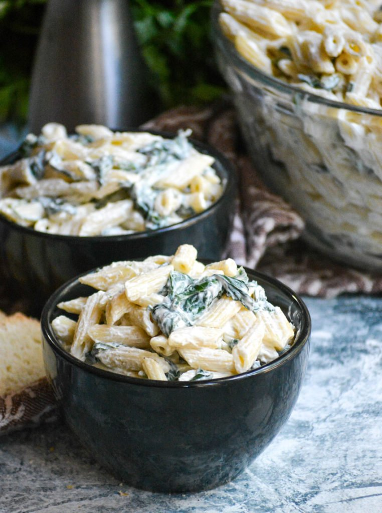 spinach dip pasta salad served in two small black bowls