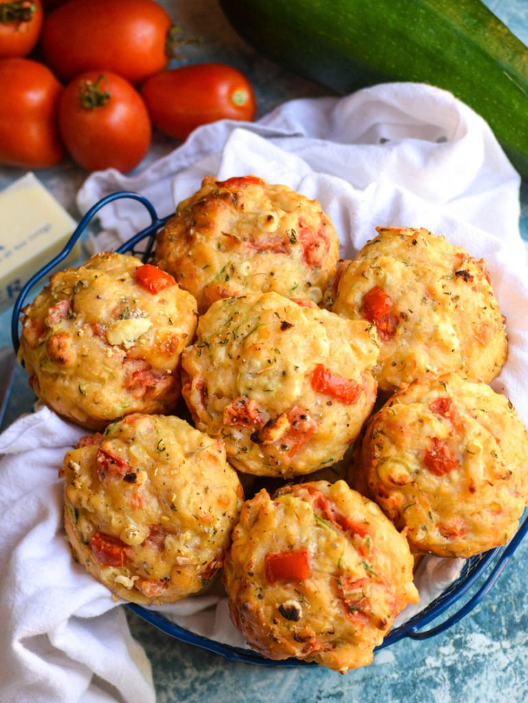 tomato zucchini feta muffins shown in a blue wire basket lined with a white cloth