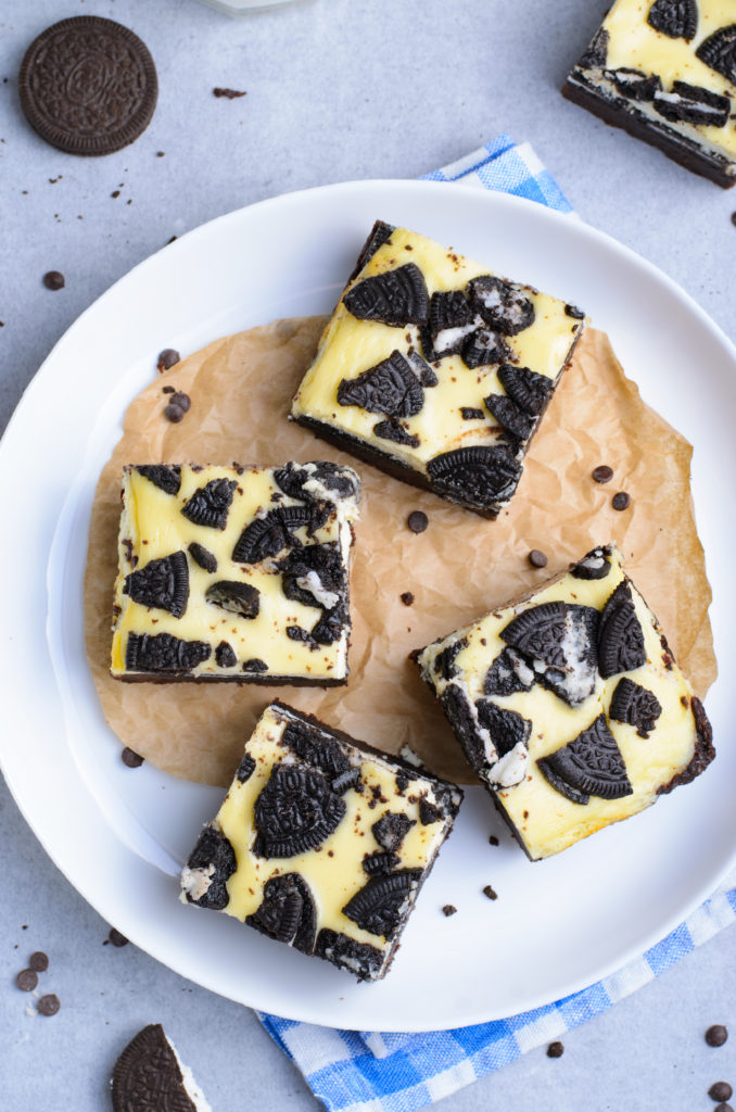 oreo cheesecake brownie squares shown on a parchment paper lined white plate