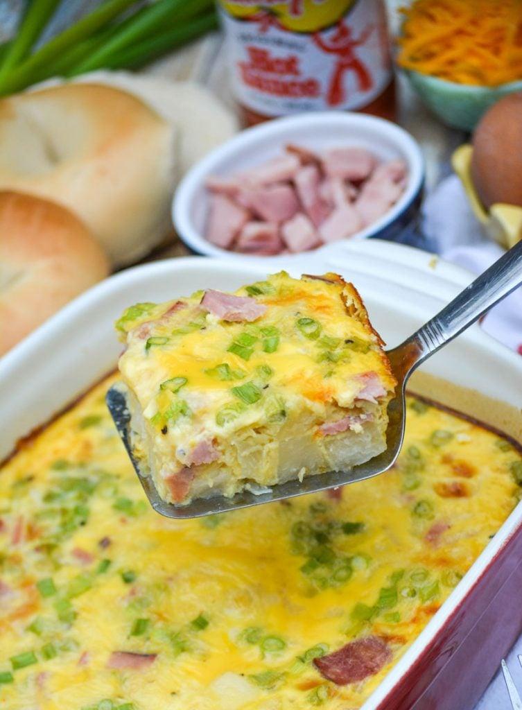 a silver spatula holding up a slice of farmer's market breakfast casserole
