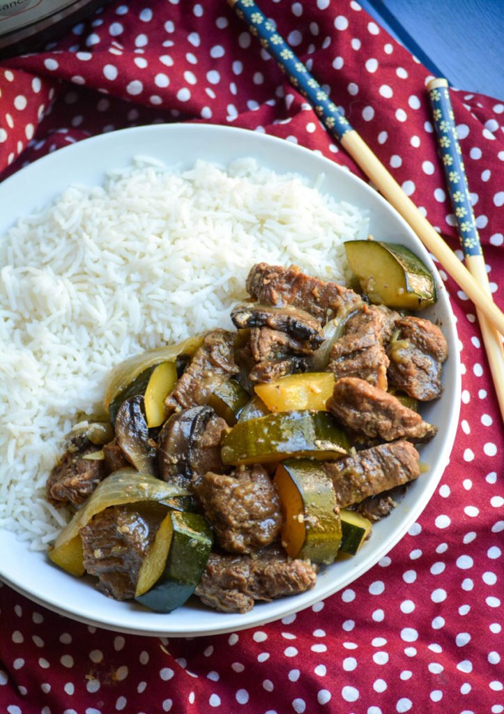 Instant Pot hibachi style steak & zucchini served with steamed white rice in a shallow white bowl