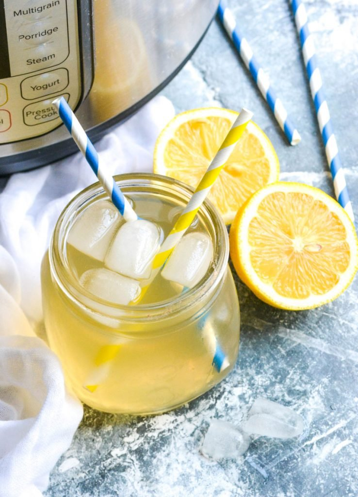 Instant pot lemonade shown in a glass jar with ice cubes and two striped paper straws