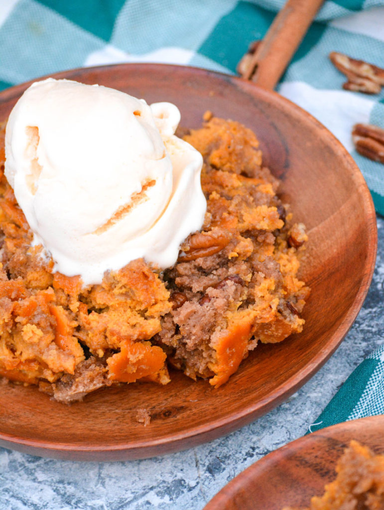 pumpkin pecan dump cake on wooden plates topped with a scoop of melting vanilla ice cream