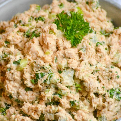 salmon salad spread in a grey bowl topped with fresh parsley leaves