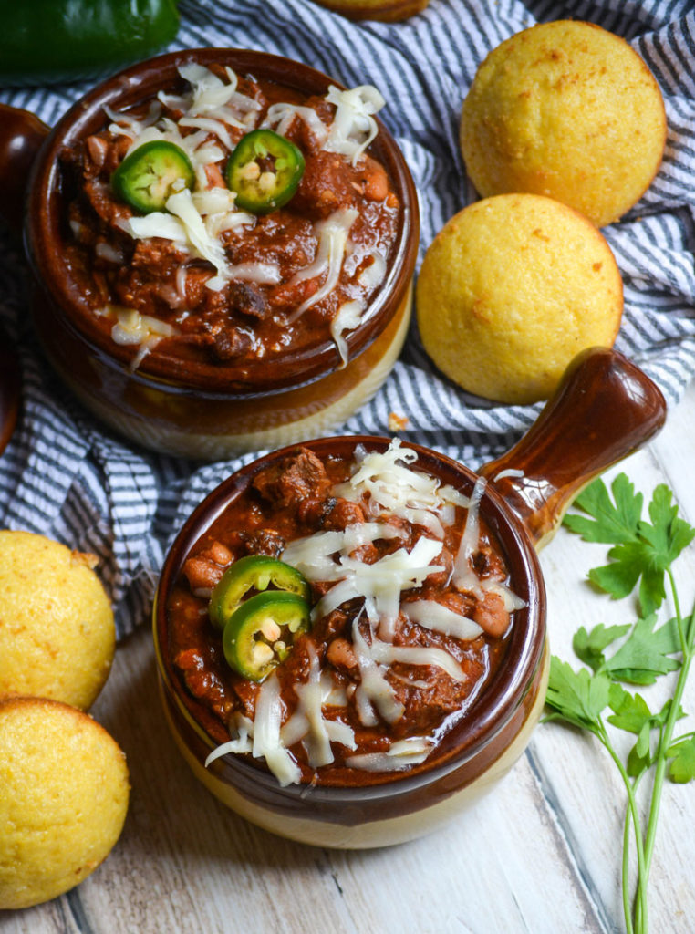 two brown crock style bowls of smoked brisket chili topped with melted shredded white cheese and fresh slices of jalapenos