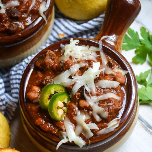 a brown crock style bowl filled with smoked brisket chili garnished with melted cheese and jalapeno slices