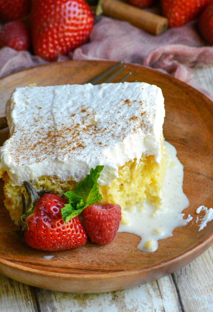 a slice of tres leches cake on a small wooden plate with fresh berries