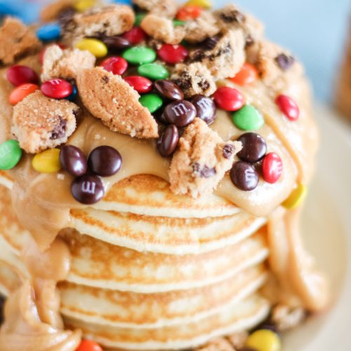 a stack of monster cookie pancakes on a white plate