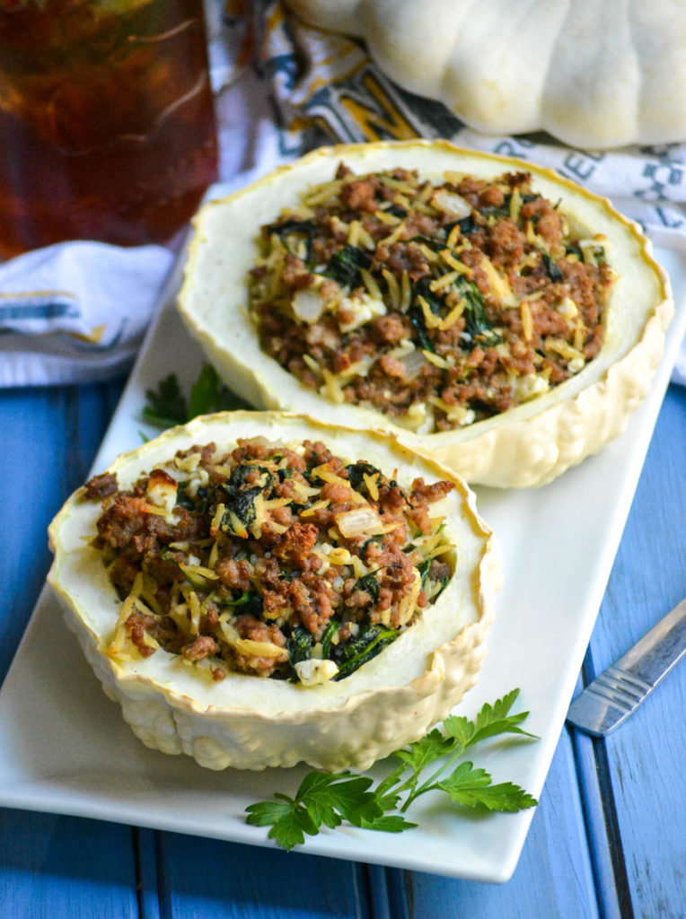 stuffed pattypan squash on a white platter with green herbs on the side