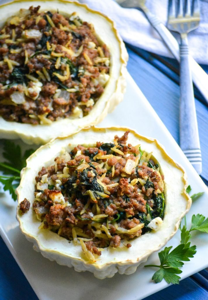 stuffed patty pan squash on a white platter with green herbs on the side