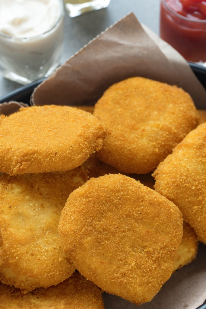 a pile of homemade nuggets on a cloth lined black dish