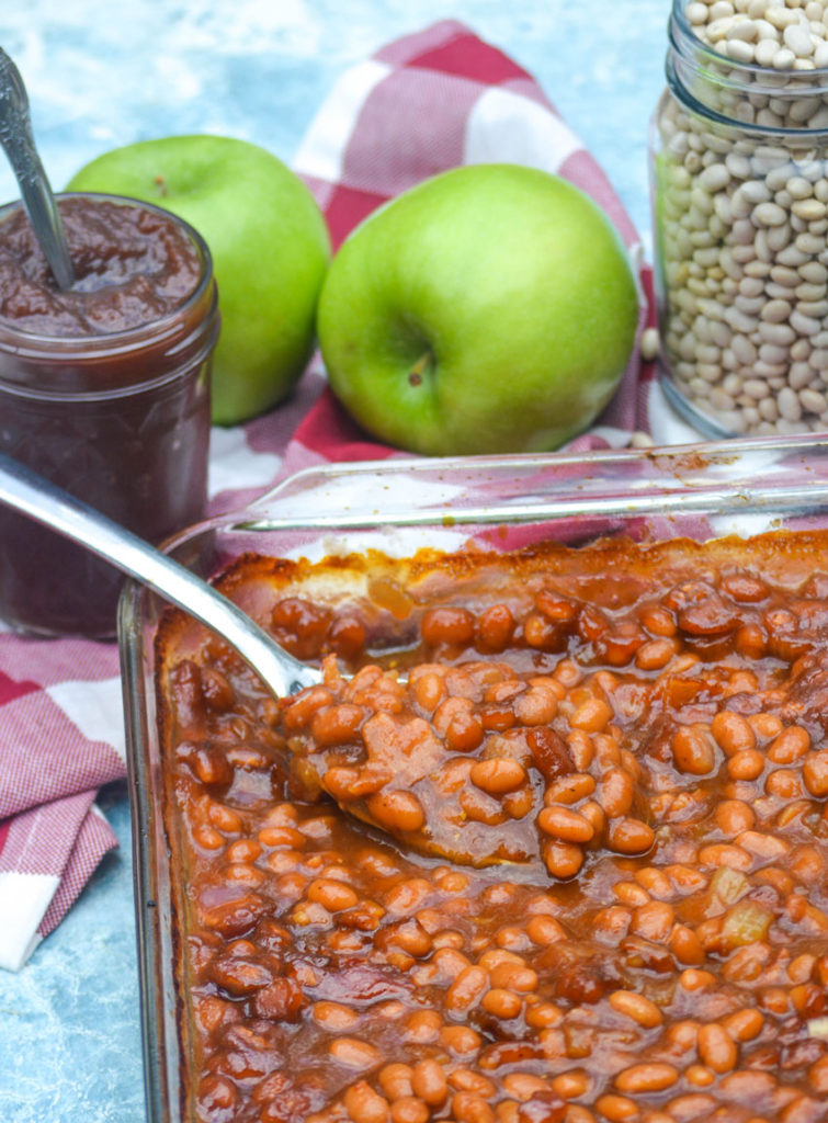 a silver spoon shown in a dish of apple butter baked beans