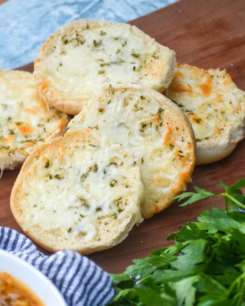 cheesy cheeseburger bun garlic toast on a wooden cutting board