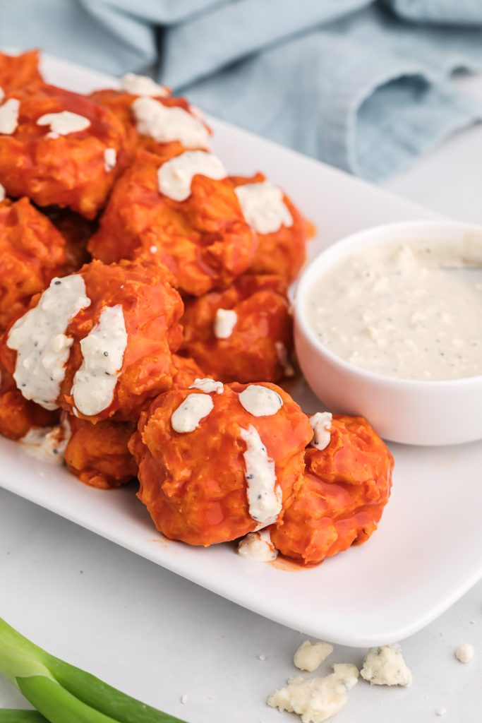 buffalo chicken meatballs on a white platter with a bowl of blue cheese dressing