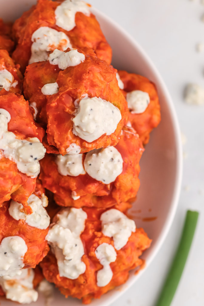 blue cheese sauce drizzled buffalo chicken meatballs in a white bowl